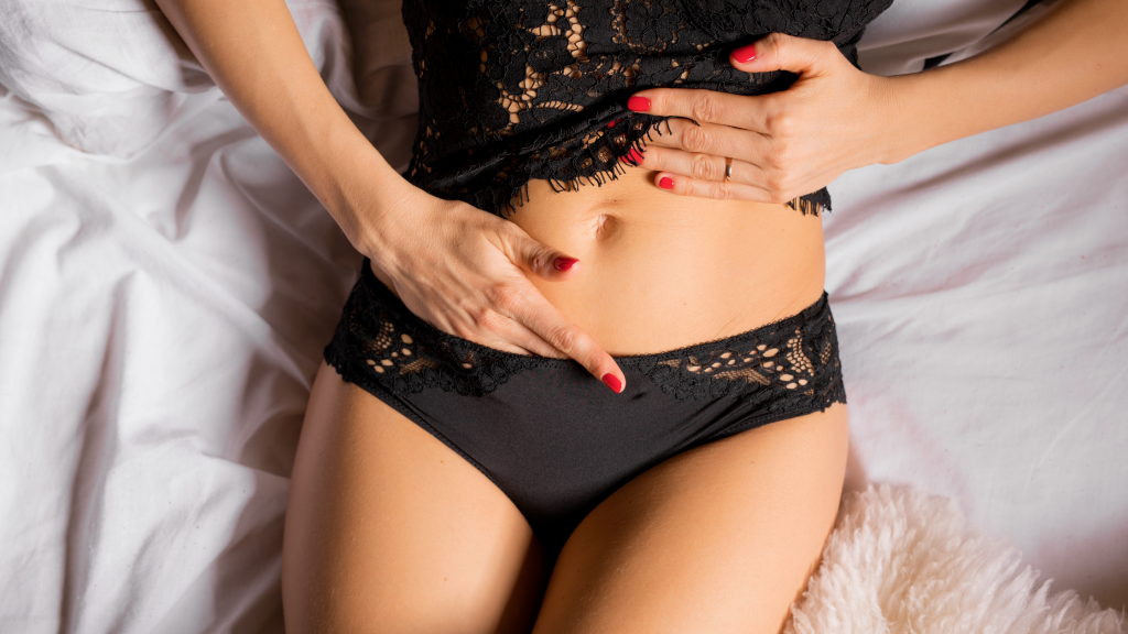 women with red nails touching herself with black lace clothes in bed