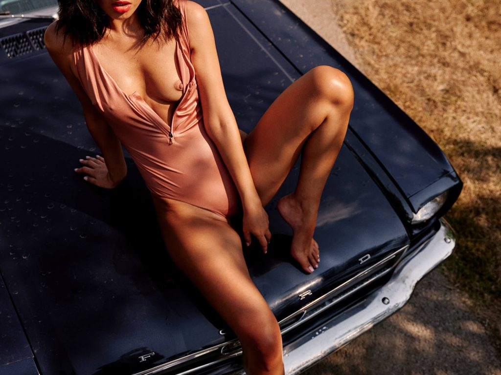 half naked lady with pink swimsuit sitting on black car
