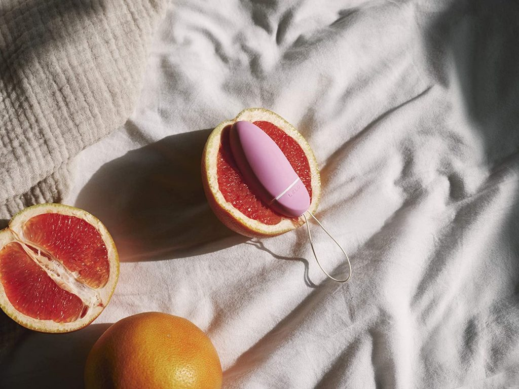 Lelo pink vibrator with grapefruits in bed